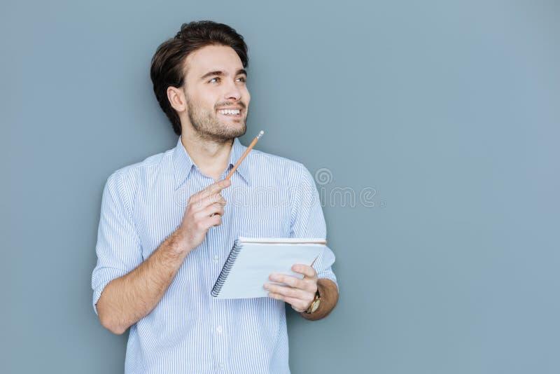 Gelukkige aardige mens die zijn notitieboekje houden stock afbeeldingen