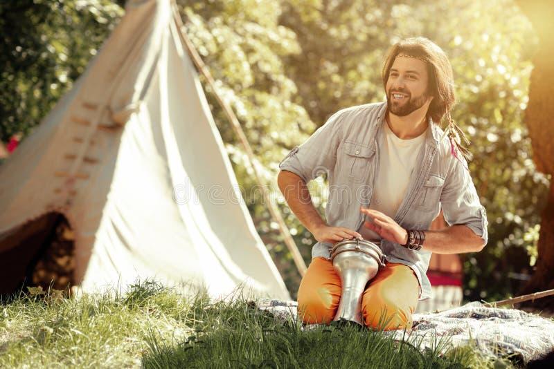 Gelukkige aardige mens het spelen trommels in het park stock afbeelding