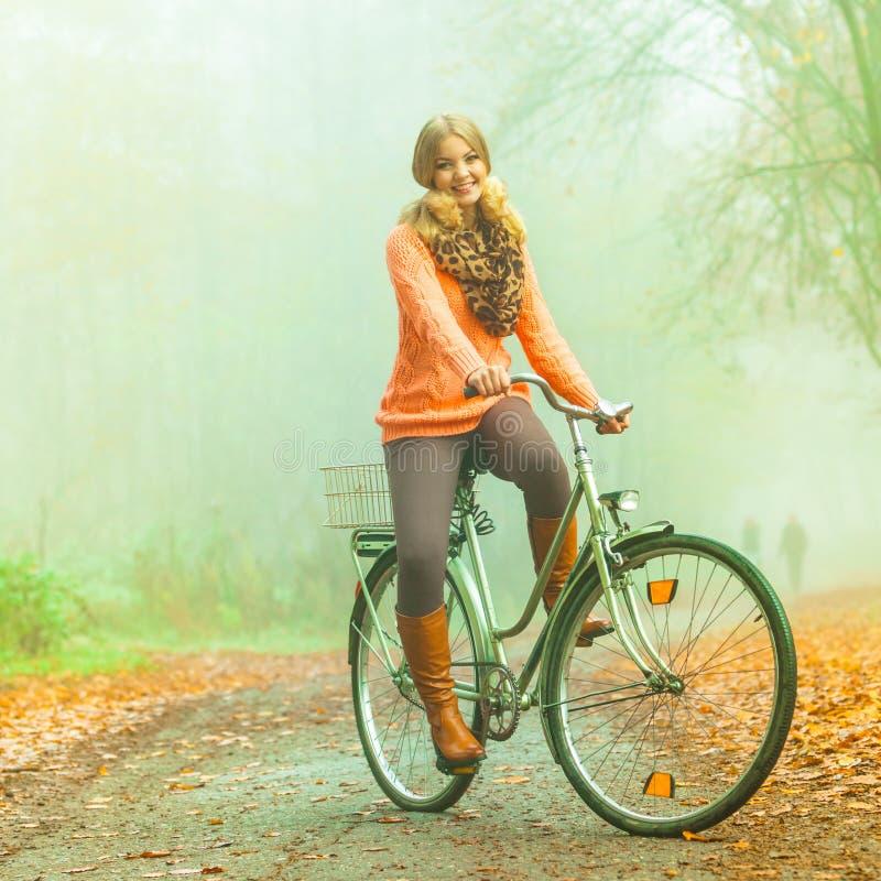 Gelukkige actieve vrouwen berijdende fiets in de herfstpark stock foto's