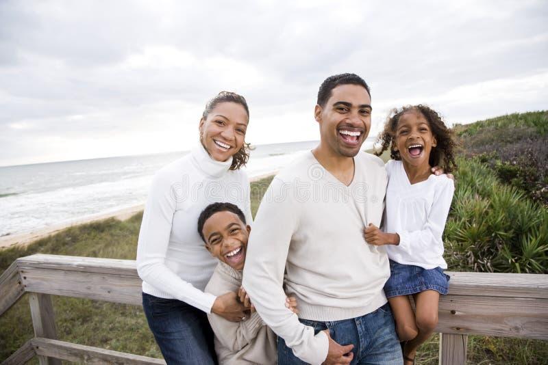 Gelukkige Afrikaans-Amerikaanse familie van vier op strand stock fotografie