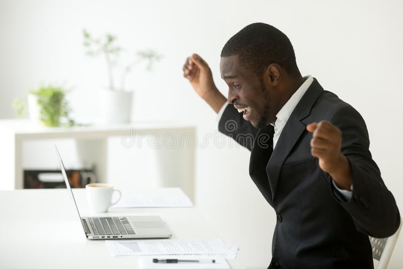 Gelukkige Afrikaans-Amerikaanse zakenman het vieren succes online wi stock fotografie