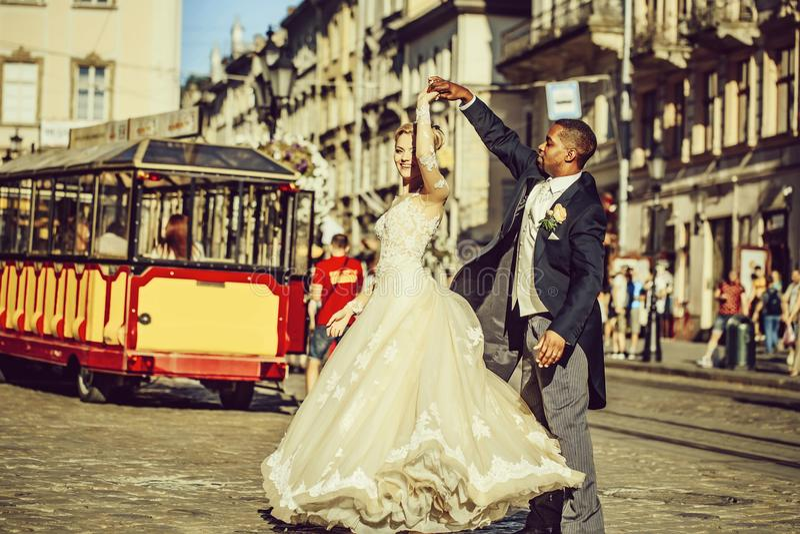 Gelukkige Afrikaanse Amerikaanse bruidegom en leuke bruid die op straat dansen royalty-vrije stock fotografie