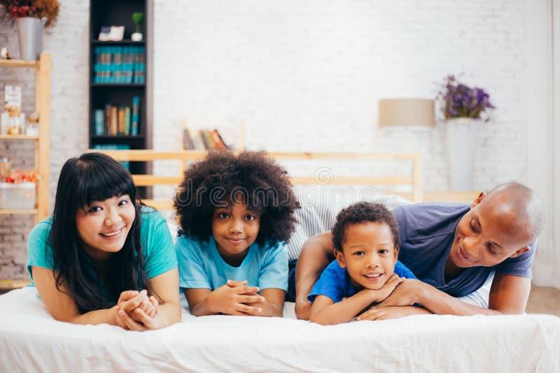 Gelukkige Afrikaanse Amerikaanse familie die thuis op bed leggen die, gelukkig aan elkaar spreken Ouderschap en familieconcept royalty-vrije stock foto's