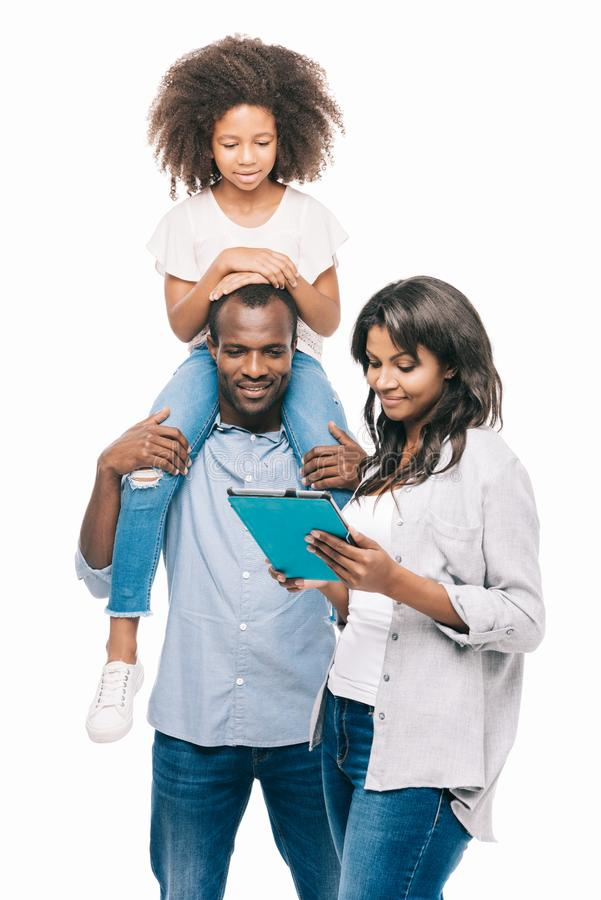 gelukkige Afrikaanse Amerikaanse familie met één kind die digitale tablet samen gebruiken royalty-vrije stock afbeeldingen