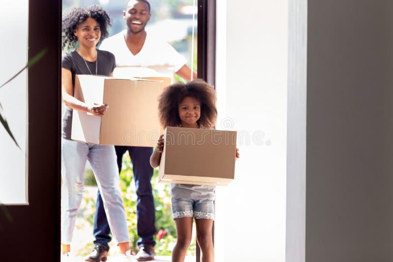 Gelukkige Afrikaanse Amerikaanse familie met dochter het binnengaan in nieuw huis stock afbeelding