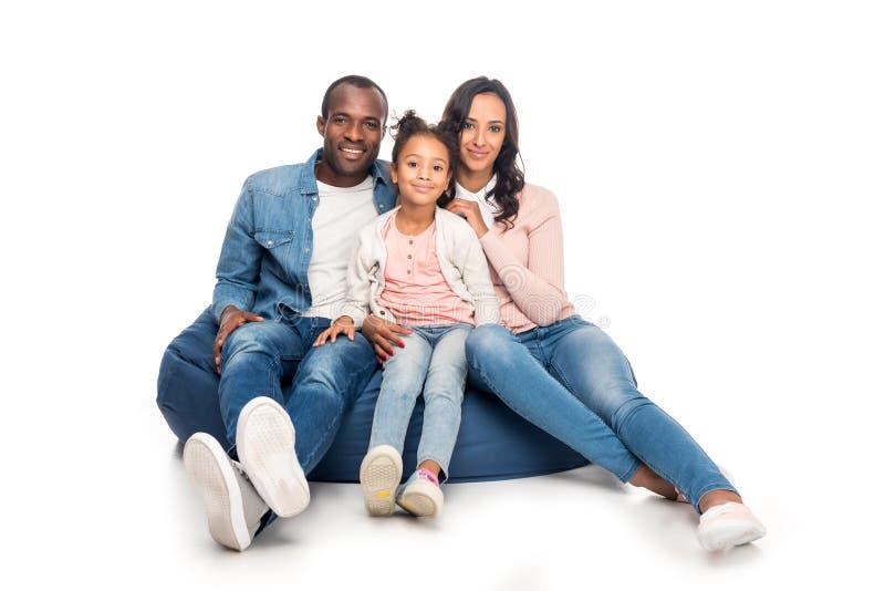 gelukkige Afrikaanse Amerikaanse familiezitting op kinderspelstoel en het glimlachen bij camera stock fotografie