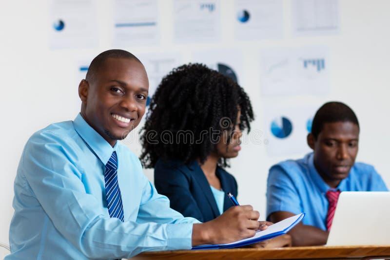 Gelukkige Afrikaanse Amerikaanse financiële adviseur met commercieel team stock fotografie