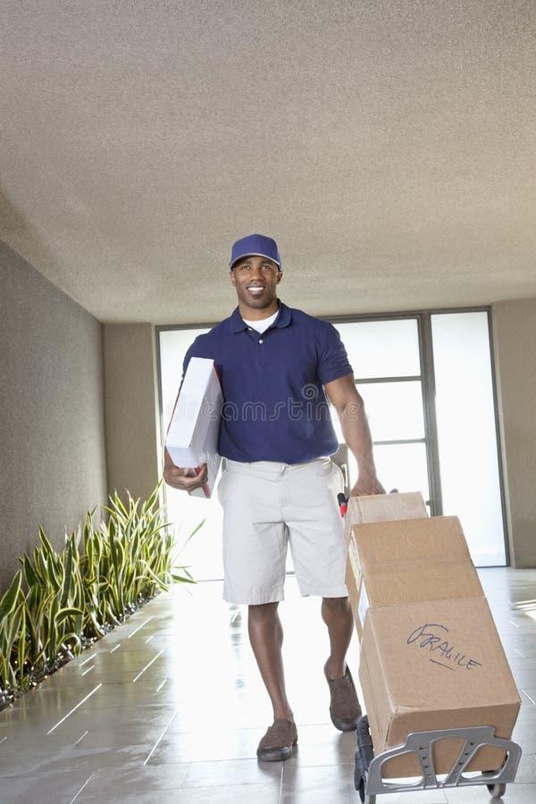 Gelukkige Afrikaanse Amerikaanse leveringsmens met pakketten stock foto's