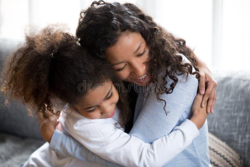 Gelukkige Afrikaanse Amerikaanse mamma en dochteromhelzing die vrede maken stock foto's