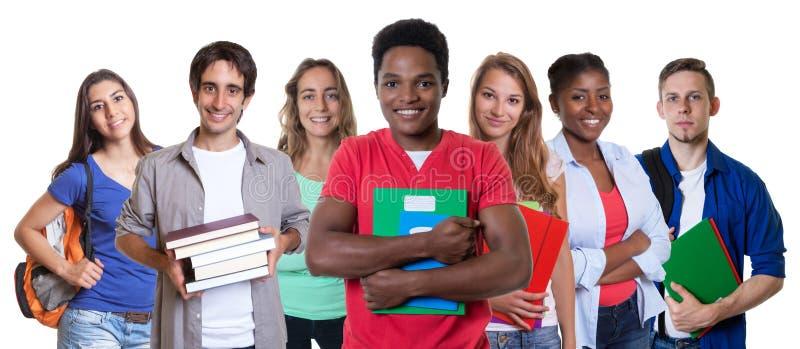 Gelukkige Afrikaanse Amerikaanse mannelijke student met groep studenten stock fotografie