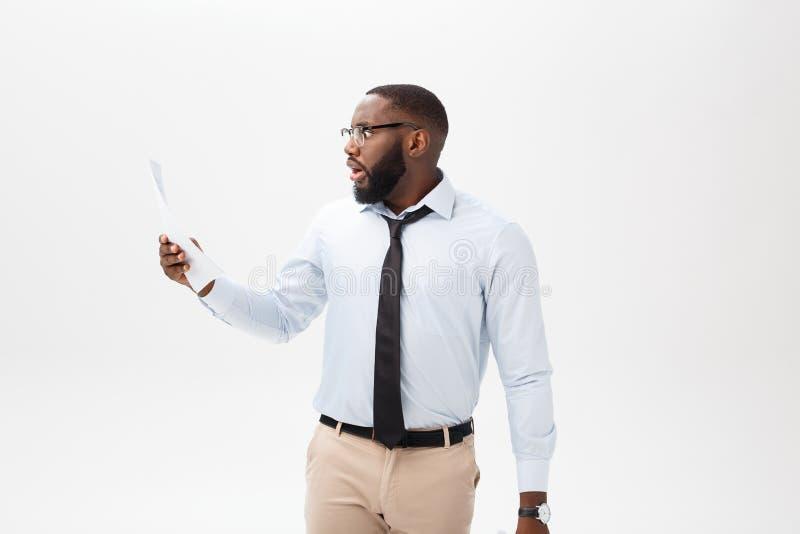 Gelukkige Afrikaanse Amerikaanse mens die documaent document over geïsoleerde witte achtergrond met een verrassing en schokgezich royalty-vrije stock foto's