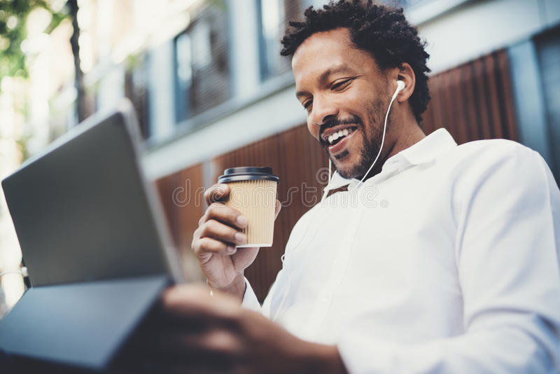 Gelukkige Afrikaanse Amerikaanse mens die in oortelefoons videovraag via elektronisch aanrakingsstootkussen maken met in hand kof royalty-vrije stock foto