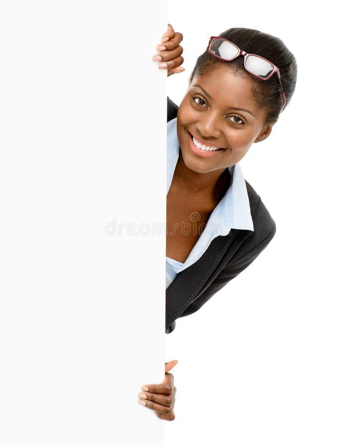 Gelukkige Afrikaanse Amerikaanse onderneemster die witte billbaord geïsoleerd houden stock foto