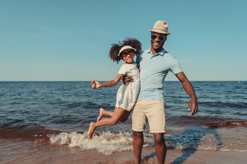 gelukkige Afrikaanse Amerikaanse vader en dochter die in zonnebril bij camera glimlachen stock foto's