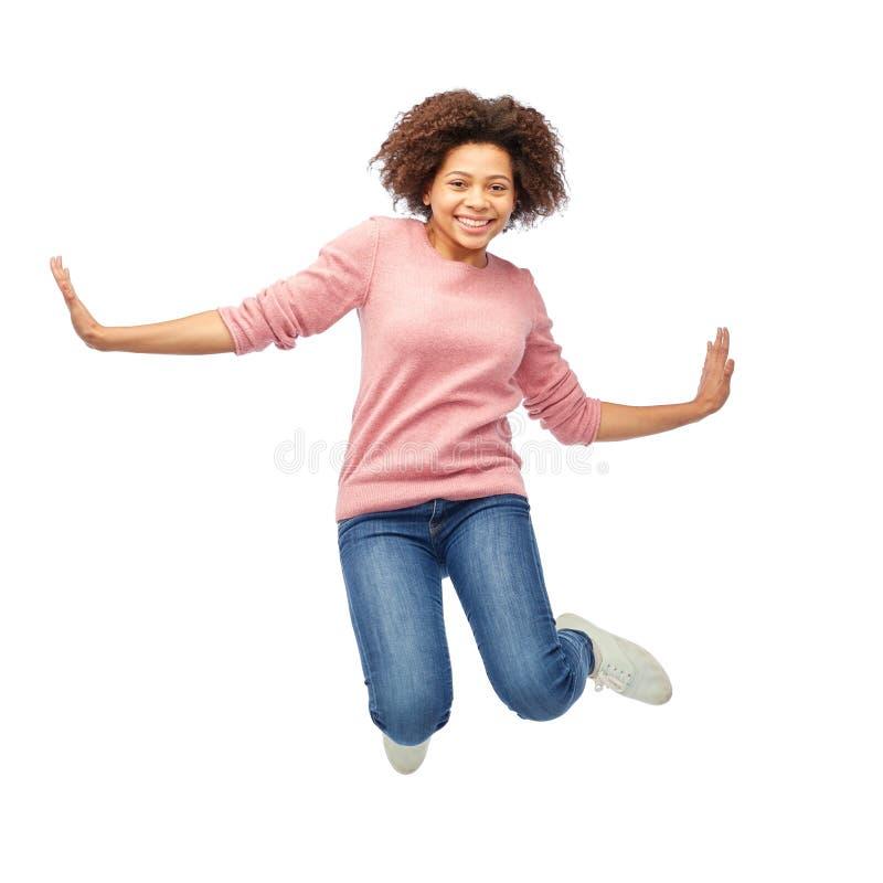 Gelukkige Afrikaanse Amerikaanse vrouw die over wit springen royalty-vrije stock afbeelding
