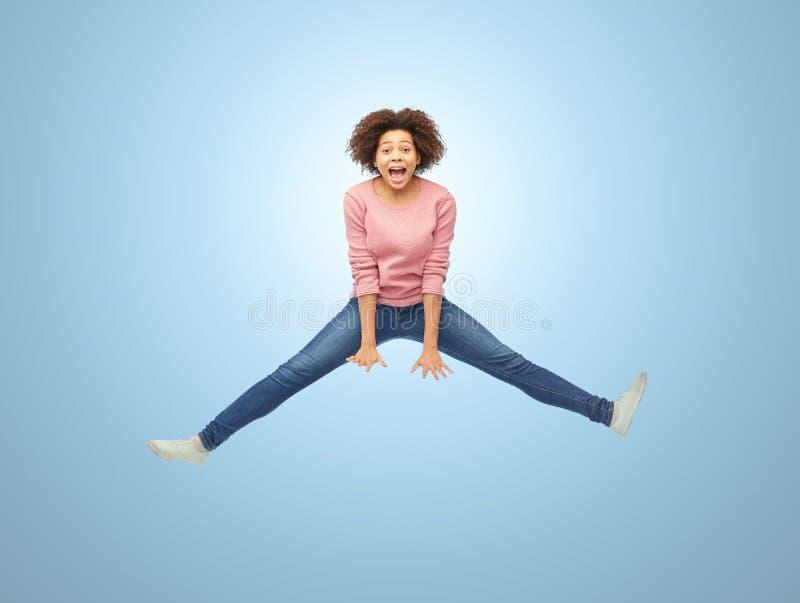 Gelukkige Afrikaanse Amerikaanse vrouw die over wit springen stock afbeelding