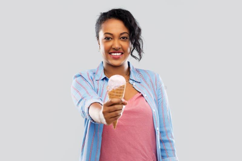 Gelukkige Afrikaanse Amerikaanse vrouw met roomijskegel stock afbeelding