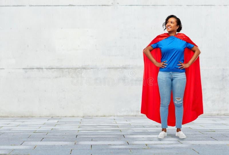 Gelukkige Afrikaanse Amerikaanse vrouw in superhero rode kaap royalty-vrije stock afbeeldingen