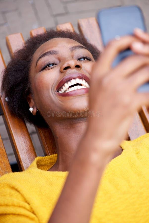 Gelukkige Afrikaanse Amerikaanse vrouwenzitting die buiten en cellphone bekijken royalty-vrije stock afbeeldingen