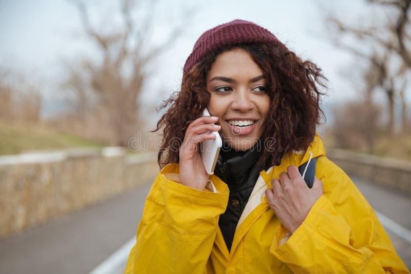 Gelukkige Afrikaanse jonge dame die gele laag dragen die telefonisch spreken royalty-vrije stock fotografie