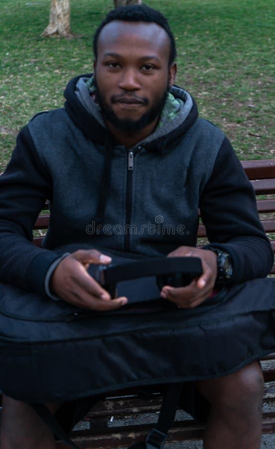 Gelukkige Afrikaanse jonge kerel met een baard en hoofdtelefoons in een park stock foto's