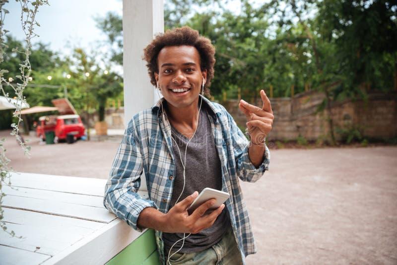Gelukkige Afrikaanse jonge mens die aan muziek van celtelefoon luisteren royalty-vrije stock afbeeldingen