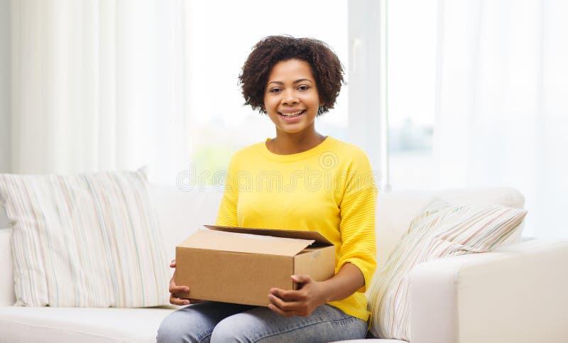 Gelukkige Afrikaanse jonge vrouw met pakketdoos thuis royalty-vrije stock fotografie