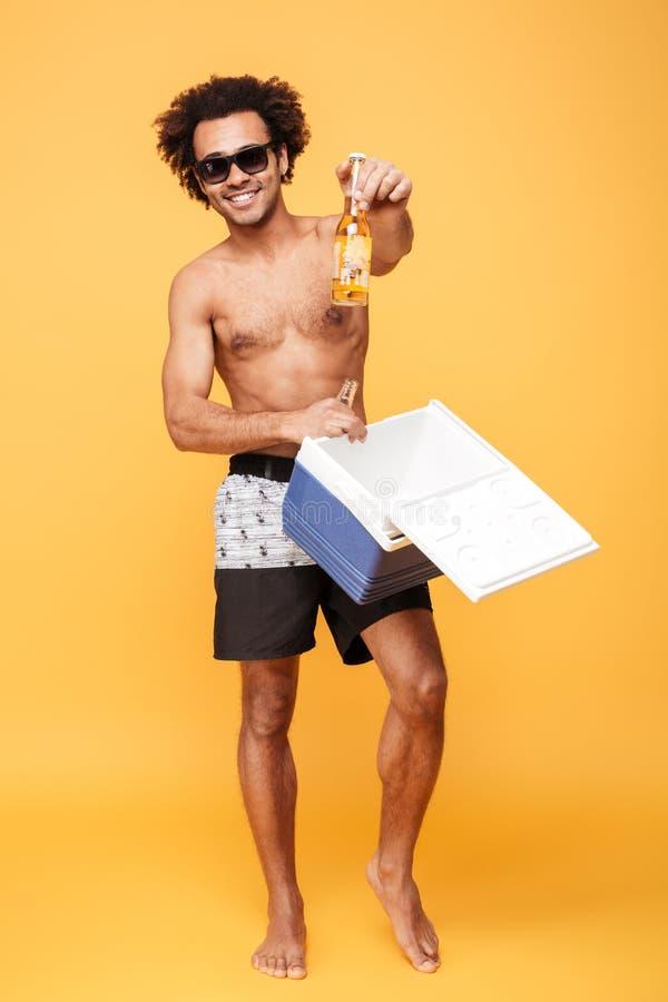 Gelukkige Afrikaanse kerel in zonnebril die bierfles in een koelbox zetten stock foto's