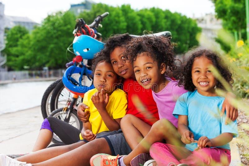 Gelukkige Afrikaanse kinderen die na het cirkelen rusten stock afbeelding