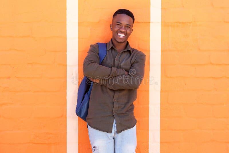 Gelukkige Afrikaanse mannelijke student die zich tegen oranje muur met zak bevinden stock afbeelding