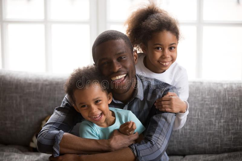 Gelukkige Afrikaanse papa en het gemengde portret van raskinderen thuis stock afbeelding