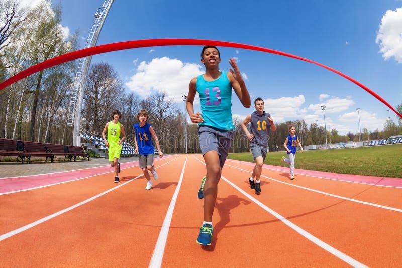Gelukkige Afrikaanse sprinter die aan de afwerkingslijn lopen stock foto's