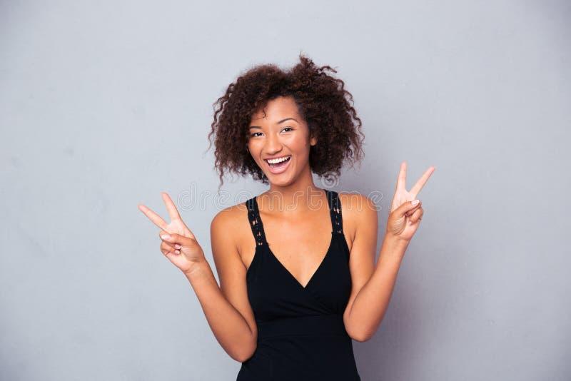 Gelukkige Afrikaanse vrouw die overwinning met vingers tonen royalty-vrije stock fotografie