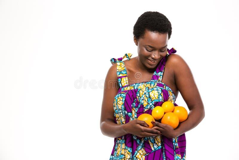 Gelukkige Afrikaanse vrouw in heldere sundress met sinaasappelen en citroenen royalty-vrije stock afbeelding