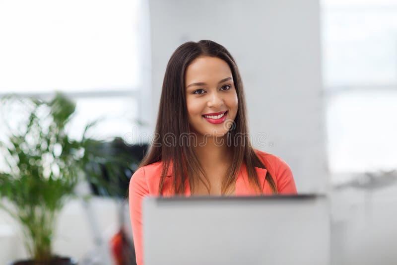 Gelukkige Afrikaanse vrouw met laptop computer op kantoor stock afbeeldingen