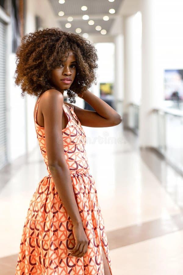 Gelukkige Afrikaanse vrouw in mooie kleding in een winkelcomplex stock foto