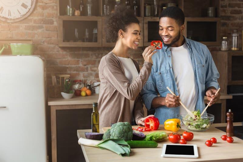 Gelukkige Afrikaanse vrouwen voedende echtgenoot terwijl het koken royalty-vrije stock afbeelding