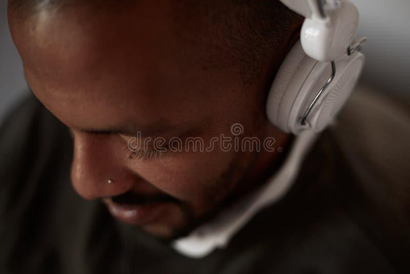 Gelukkige Afrikaanse zwarte mens die aan muziek het ontspannen op banklaag luisteren met hoofdtelefoons in huiswoonkamer Het port royalty-vrije stock afbeeldingen