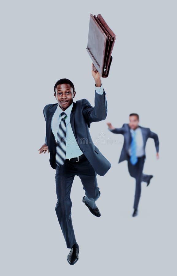 Gelukkige Afro-Amerikaanse mens die met een in hand aktentas lopen op de achtergrond zijn collega, die proberen de achterstand in stock fotografie