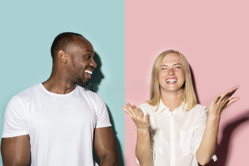Gelukkige afroman en vrouw Dynamisch beeld van Kaukasisch wijfje en afro mannelijk model op roze studio stock afbeeldingen