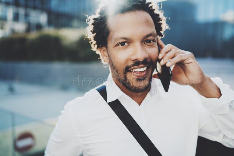 Gelukkige Amerikaanse Afrikaanse mens die mobiele telefoon met behulp van om zijn vrienden bij zonnige stad te roepen Concept gel royalty-vrije stock afbeelding
