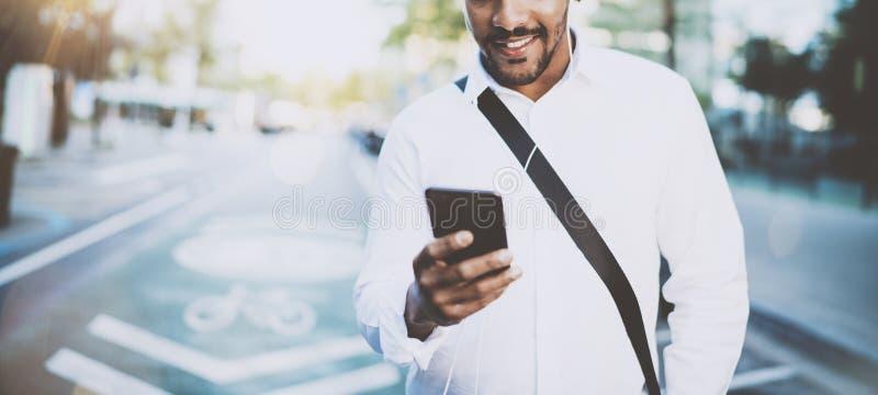 Gelukkige Amerikaanse Afrikaanse mens die smartphone gebruiken openlucht Portret van de jonge zwarte vrolijke mens die een smsber royalty-vrije stock foto