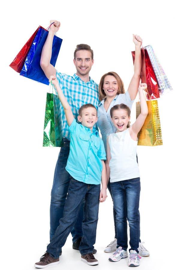 Gelukkige Amerikaanse familie met kinderen die het winkelen zakken houden royalty-vrije stock afbeeldingen
