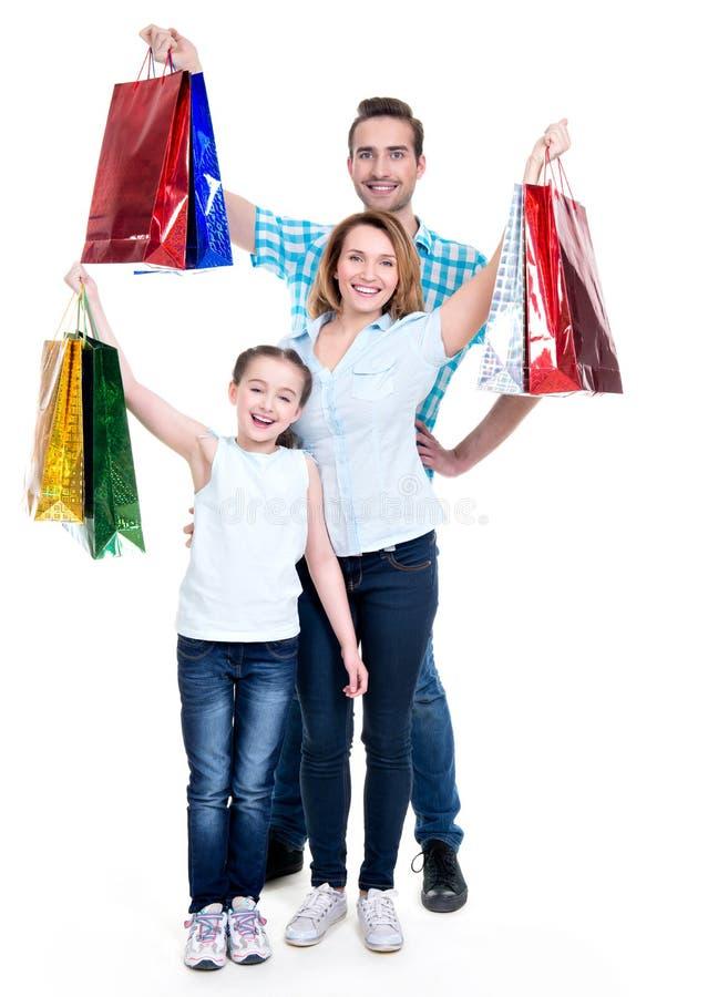 Gelukkige Amerikaanse familie met kindholding het winkelen zakken stock fotografie