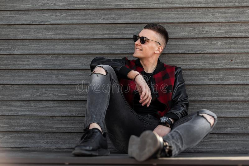 Gelukkige Amerikaanse jonge hipstermens in een modieus geruit jasje met leerkokers in gescheurde modieuze jeans in tennisschoenen royalty-vrije stock fotografie