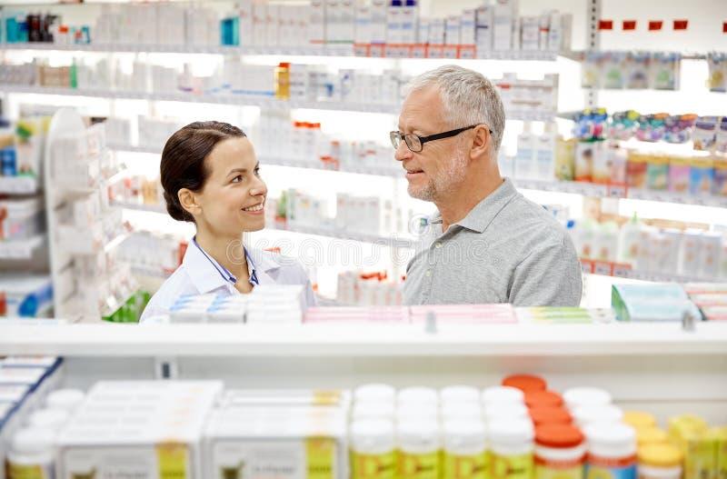 Gelukkige apotheker die aan de hogere mens bij apotheek spreken stock afbeelding