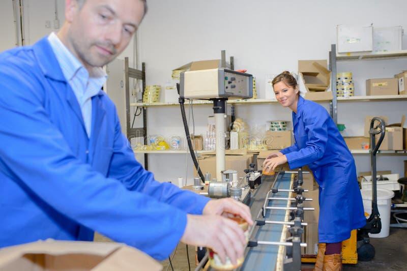 Gelukkige arbeiders op fabriekslijn stock fotografie