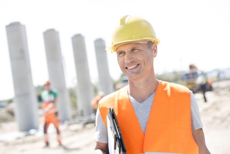 Gelukkige architect die weg terwijl het houden van klembord bij bouwwerf kijken royalty-vrije stock foto's