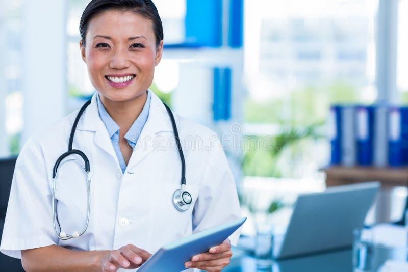 Gelukkige arts die bij de tablet van de cameraholding glimlachen stock fotografie