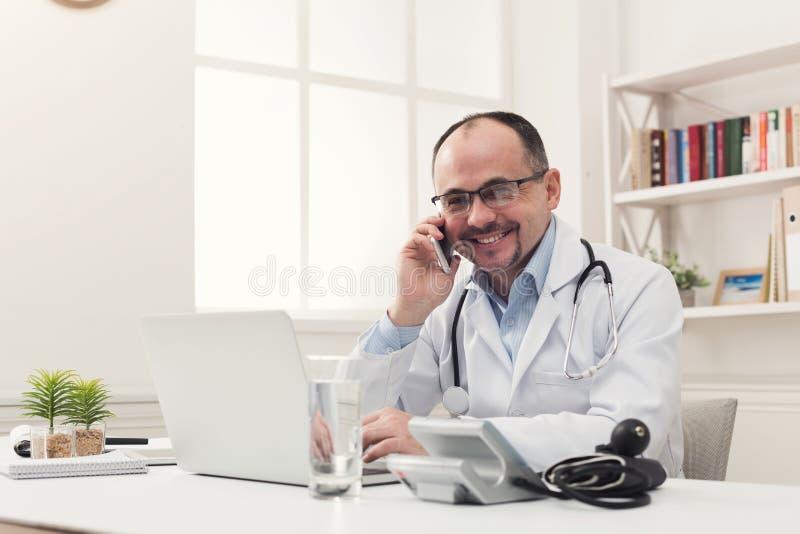 Gelukkige arts die op telefoon met zijn patiënt spreken stock foto's